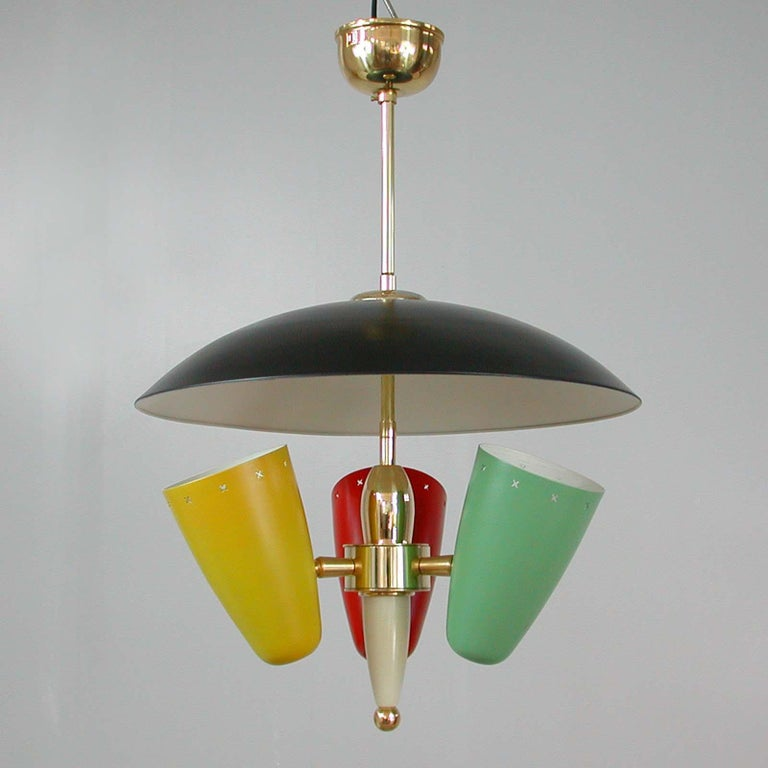 This very rare multi-color reflecting chandelier was made in Italy in the 1950s in the manner of Stilnovo.  The chandelier has got three lacquered metal shades and requires one E14 bulb per shade. The colors are red, yellow and mint. The top