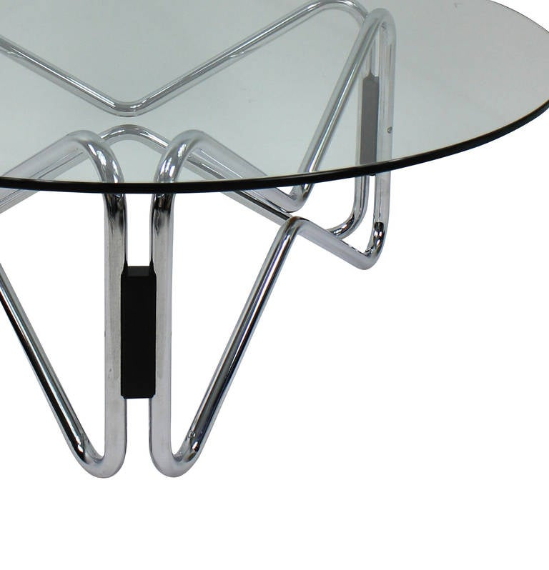 An Italian occasional table of geometric design in chrome, wood and with a circular plate glass top.