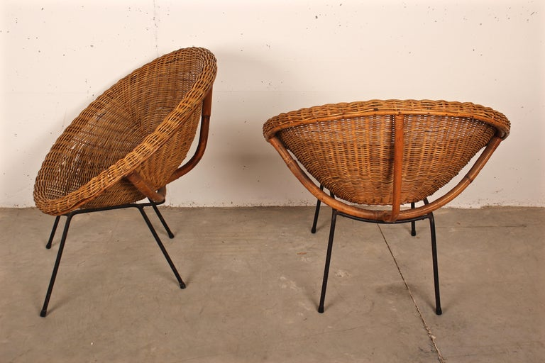 Pair of Italian 1950s armchairs in the shape of a circle in woven wicker rattan and bamboo the legs are in black lacquered metal.