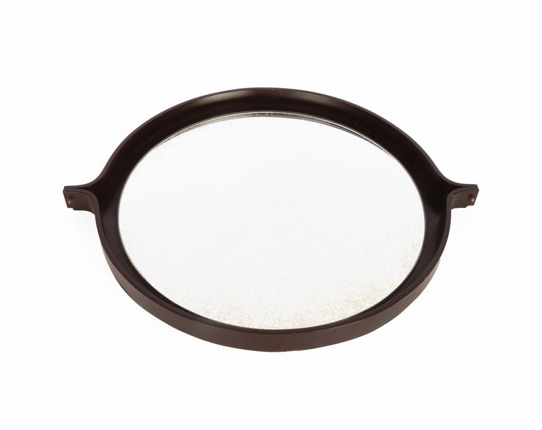 Amazing round dark brown wood mirror. This item was produced in Italy during the 1960s.  This wonderful piece is very elegant and timeless because of the simplicity of the materials and the midcentury lines.  The perfect element to enrich a