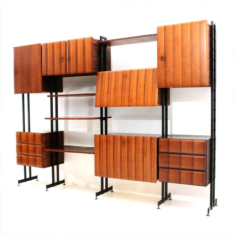 Italian manufacture library produced in the 1950s. Uprights in black painted metal with brass feet adjustable in height. Container modules in veneered wood. Front panels and drawers with tapered edges. Interior shelves in veneered wood. Bar