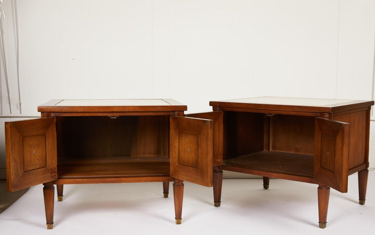 This Midcentury Italian pair of neoclassical style two-door end tables or bedside tables are made of walnut and finished on all sides. The tables are complimented by thick Italian travertine marble insets and bronze pulls and sabots. Marble marked