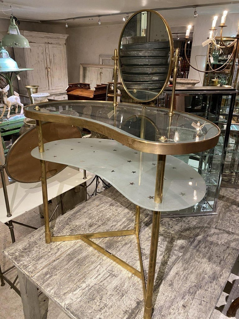Stylish midcentury French vanity table and mirror. Beautiful kidney shaped form, with a beautifully slender and elegant brass frame and two glass shelves, one being opaque and the other charmingly decorated with small stars. The oval tilting mirror