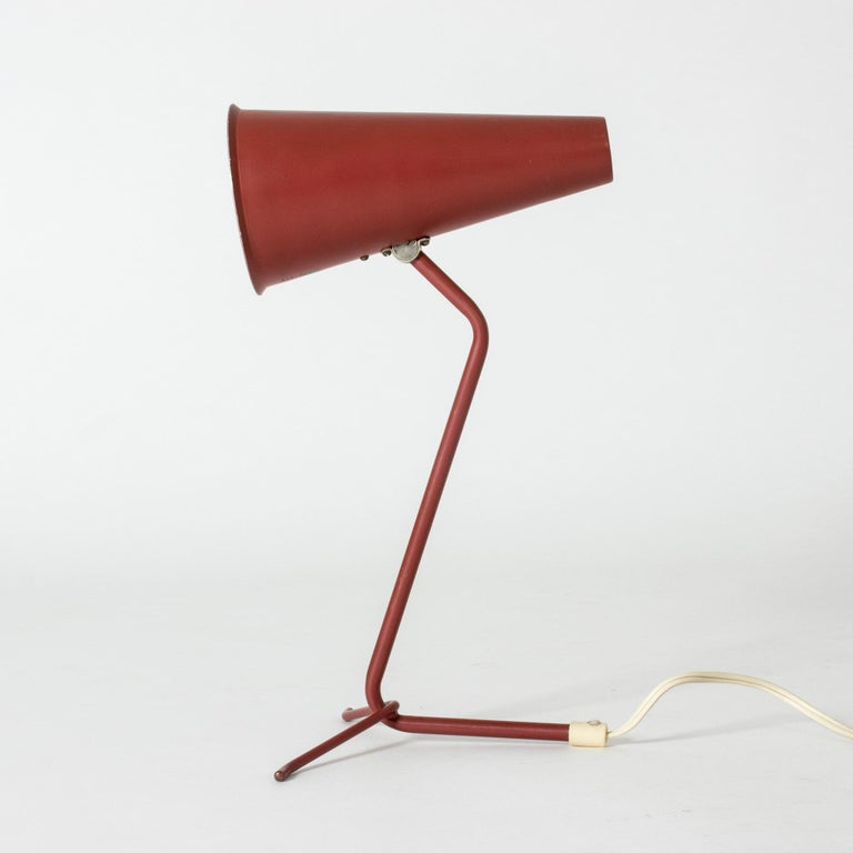 Lacquered metal table lamp from ASEA in a cool design with a long, conical shade. Dark red outside and white inside.