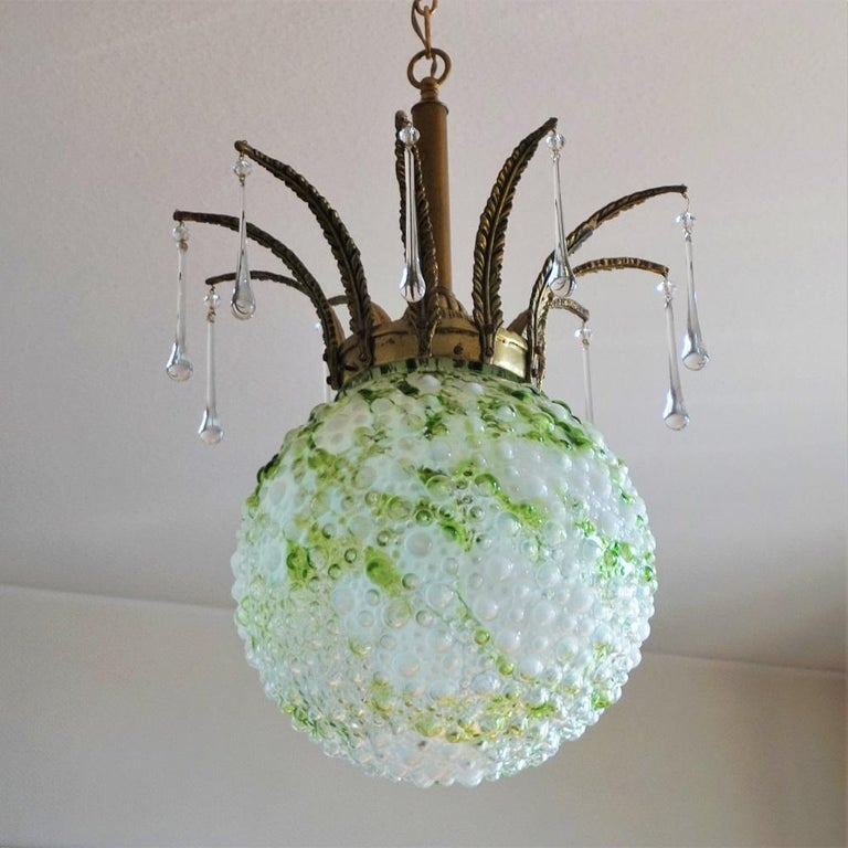 A large colored blown Murano glass ball globe chandelier, Italy, 1950s. The globe glass is thick and heavy, bronze and brass mounts with Murano glass drops. This unique and wonderful chandelier is in very good condition, aged patina to bronze, no