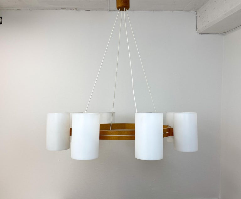 This Large chandelier was designed by Uno & Östen Kristiansson for Luxus, Sweden. The chandelier is made with eight acrylic cylinders each cylinder has its own source of light. The arms are held together with the cylinders and with cables goes to