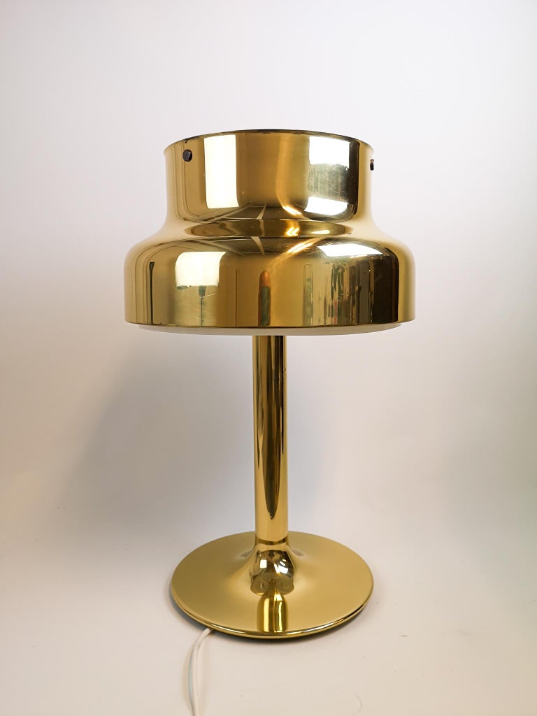 This 1960s table lamp, model Bumling, was designed by Anders Pehrson for Ateljé Lyktan in Åhus, Sweden. This table lamp with its brass features is a nice edition to your writing desk or table.   Nice working vintage condition.  Measures: H 62