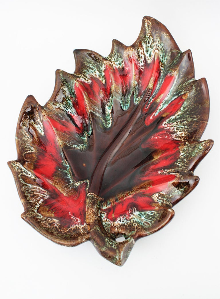Impressive and colorful extra large leaf shaped glazed ceramic platter, serving tray or centerpiece manufactured by Vallauris. France, 1950-1960s.
