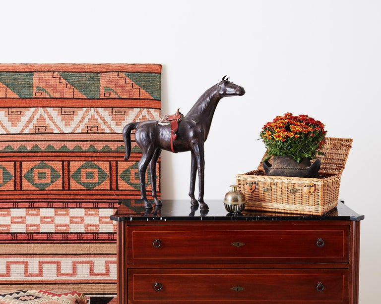 Large Mid-Century Modern handmade leather thoroughbred horse sculpture featuring a red tooled leather saddle with a shearling lining. This lovely horse has a statuesque pose with interesting glass eyes. Beautiful vintage patina on the leather.