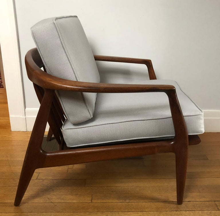 Midcentury teak lounge chair with curved back. This iconic chair was designed by Folke Ohlsson for DUX (Model 72-C). It was made in Sweden and dates back to the 1950s-1960s.