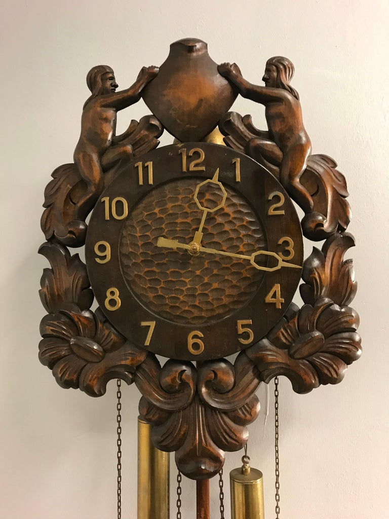 Tasteful and unique wooden wall clock with sculptural front.  The magnificent front of this midcentury era wall clock is entirely hand carved out of solid wood. It is difficult to see in a photo, but even the dial face is perfectly carved and a rare