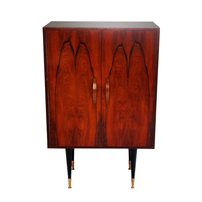 Bar cabinet made of mahogany. With conic black lacquered wooden legs, finished with brass toppers, and interior glass shelving.