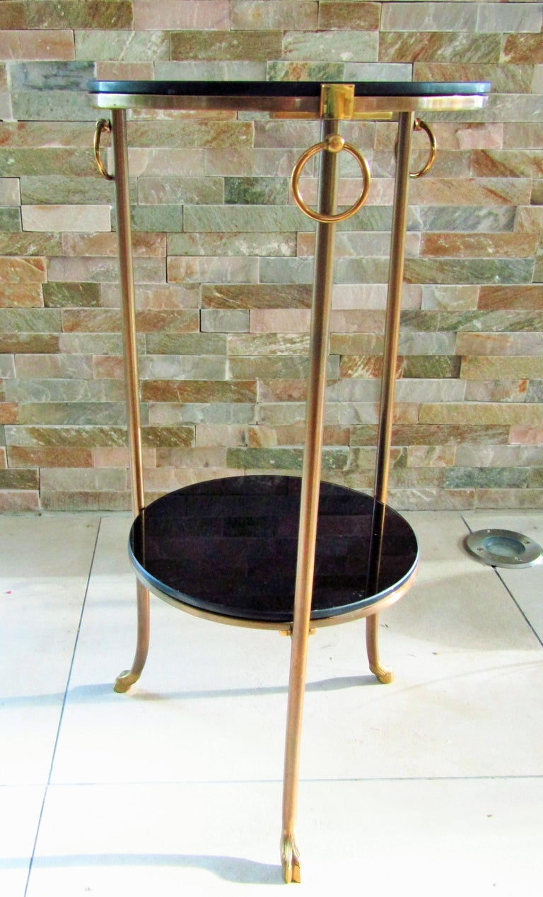 A midcentury side table signed Maison Charles, France, circa 1960. Two black glass tops, supported by three brass legs detailed with movable rings and hooved goat feet.