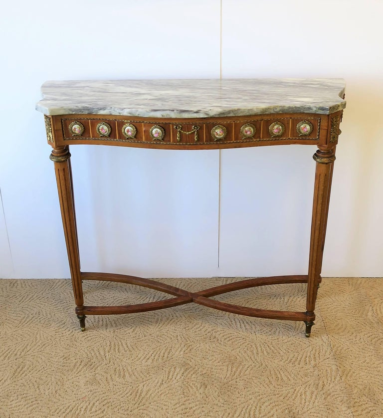 A beautiful neoclassical style console table with a grey and white marble top, wood base, and porcelain and brass ormolu mounts, circa mid-20th century, Europe. Beautiful details all around including: substantial marble top, shape of marble top,