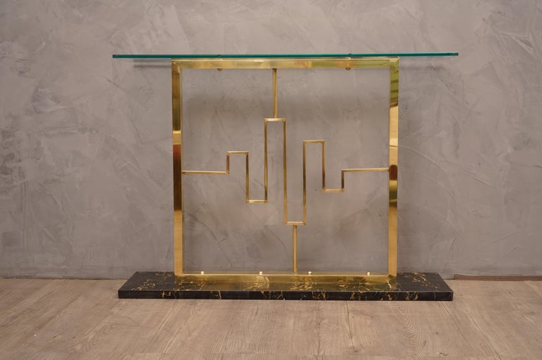 Stylish and refined pair of consoles, both for their design and for the particular pleasant marriage of three materials such as black marble, brass and glass.  The consoles are composed of a crystal top, supported by a very particular brass leg, and