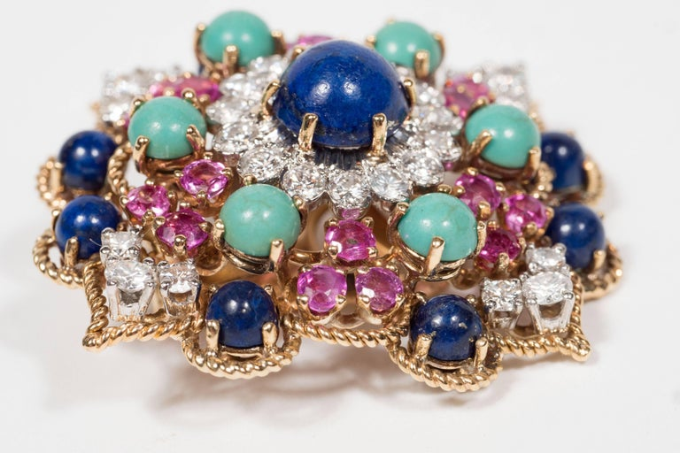 These mid-century modernist earclips are made in the United States by Marianne Oster. They are set in 18-karat yellow gold with platinum. These are set with numerous lapis lazuli and turquoise cabochons accented by numerous pink sapphires,