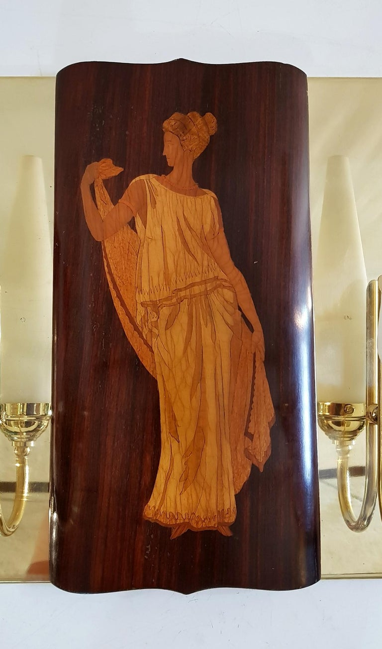 These particular wall sconces in brass was custom designed and made by a local artisan to hold the beautiful marquetry panels by Andrea Gusmai of Trani, Italy. The panels are produced in teak and boxwood depicting the Greek mythological gods Apollo