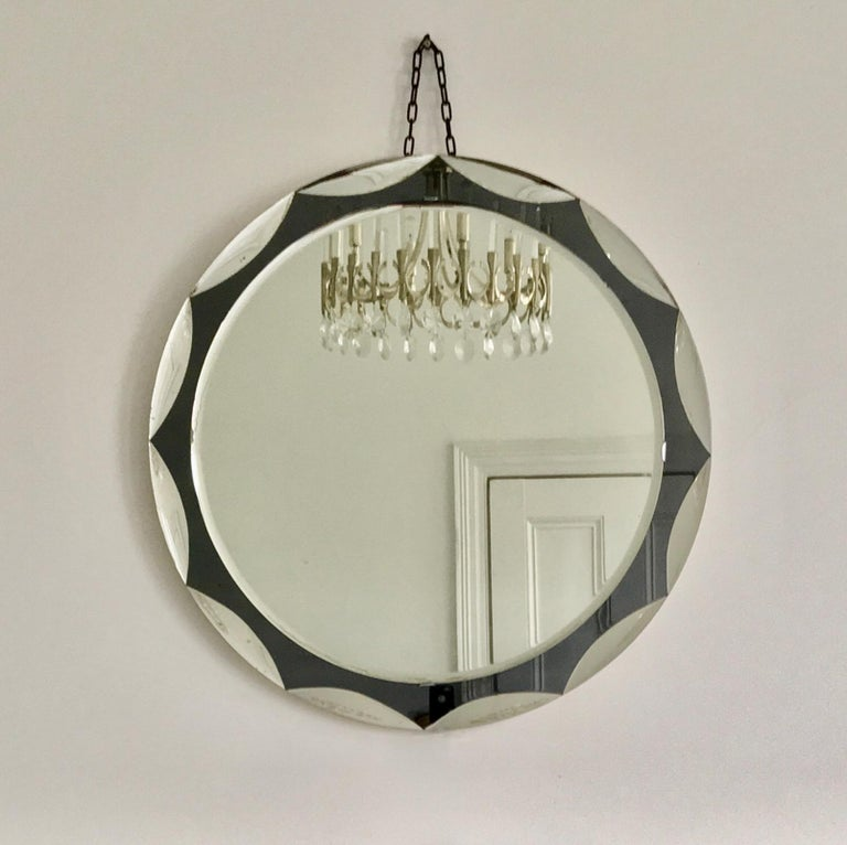 Midcentury circular mirror with large scalloped black glass edge detail. Metalvetro Galvorame of Siena, 1960s, Italy.  The mirror is a high-quality piece of good size with a double layer of mirror glass. The central glass is clear, with a beveled