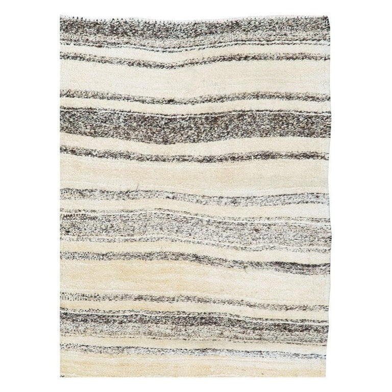 A vintage Persian flat-woven Kilim accent rug handmade during the mid-20th century using undyed wool in cream, ivory, and brown. The very neutral shades in earth tones, along with the simple striped pattern, creates a minimalistic effect that is
