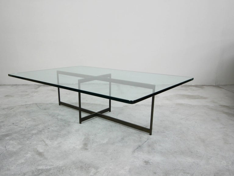 A beautiful midcentury bronze coffee table. Such a simple, yet modern and elegant piece. A minimalistic tee shape bronze frame with a gorgeous piece of rectangular glass.   Bronze has the most beautiful patina. Left as found, could be polished to