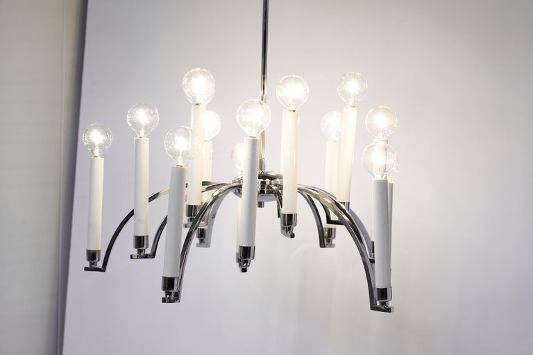 Mid-20th century chandelier made of chrome with 14 downswept arms supporting modern candlesticks holding chandelier bulbs. The chandelier was manufactured in the 1970s by Lightolier.