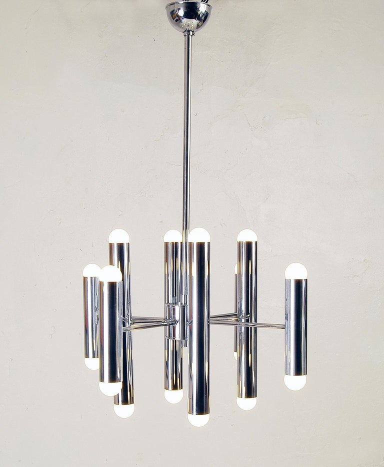 Large 1970s Italian Sciolari style chrome ceiling lamp comprising of four tall chrome tubes and four shorter tubes, each tube with a bulb at the top and bottom making 16 in total.