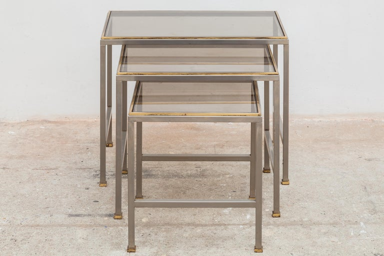 Vintage mid-century nesting tables. Modernist silver and brass tone frames with smoked glass tops.Dimensions:Small:32W x 34H x 32D cm Med: 42W x 38H x 32D cm Large: 52W x 42H x 32D cm.