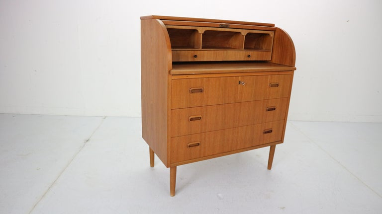This iconic midcentury Swedish modern teak cylinder rolltop secretary- desk- cabinet is made in 1970's Sweeden by Egon Ostergaard designer and manufactured by Markaryds Mobelindustri manufacture. 