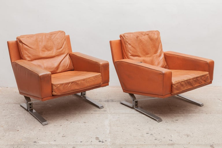 Vintage midcentury very nice club chairs. Patinated cognac leather. Wide comfortable seat and armrests. These high quality chairs are made of a massive stainless steel base. Good nice patina to the leather, signs of wear and age but not rips.