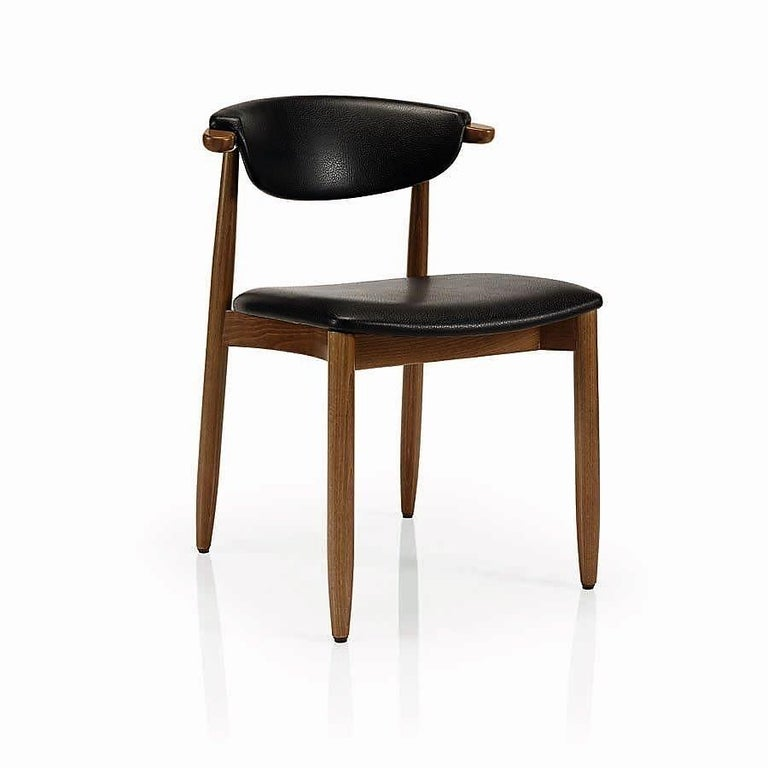 Mid-Century Modern curved back dining chairs upholstered in black faux leather.  Crafted of solid heavy full grain hardwood with walnut finish. Perfect for either casual or formal dining room or kitchen.  This chair is heavily constructed and