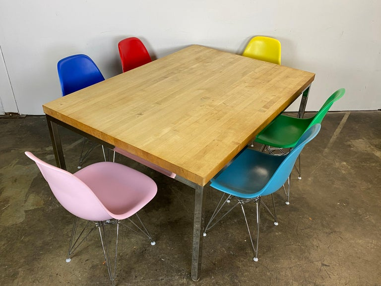 Mid-Century Modern dining set featuring maple butcher block top on steel frame. Six vintage authentic signed Herman Miller Eames fiberglass shell chairs. Originally upholstered, these have been stripped and recoated in fun colors. New chrome Eiffel