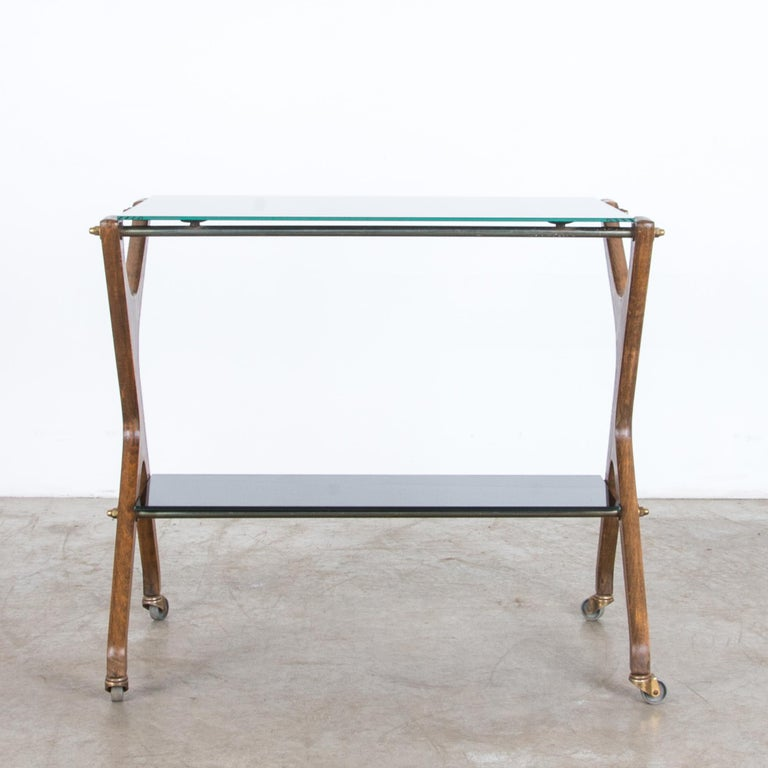 From France circa 1960, a timeless bar cart in hardwood, brass, and glass. High quality materials are elegantly arranged with a Modernist flair. Brass hardware is stylish and practical, giving a sturdy support and precise movement, supporting a