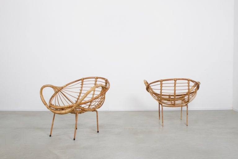 Set of sculptural rattan armchairs in very good condition.  The chairs have a elegant basket form seat and large rounded armrests.  The frame is made from steel and is covered in rattan.  The chairs have been fully restored by a rattan