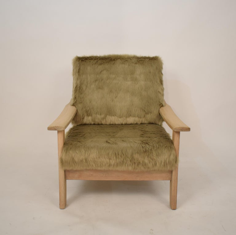 This cool Mid-Century Modern Scandinavian armchair was made circa 1970. It is made out of solid Light oakwood and was recently  upholstered in faux fur. It has this special big foot look! A unique piece which is a great eyecatcher for your
