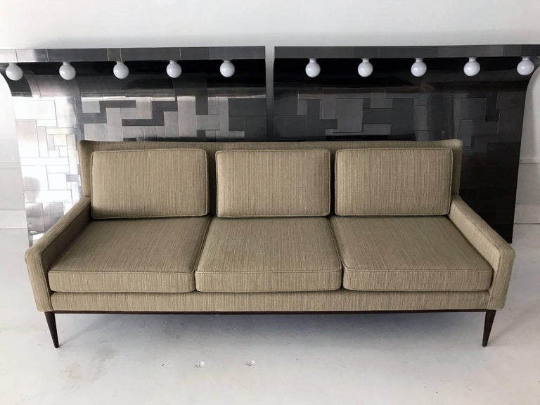 A midcentury three-seat sofa by Paul McCobb for Directional, model 1301, circa 1950s-1960s. A very clean look with a design nodding to the wing back chair. It features three removable back and seat cushions on a conforming upholstered frame,