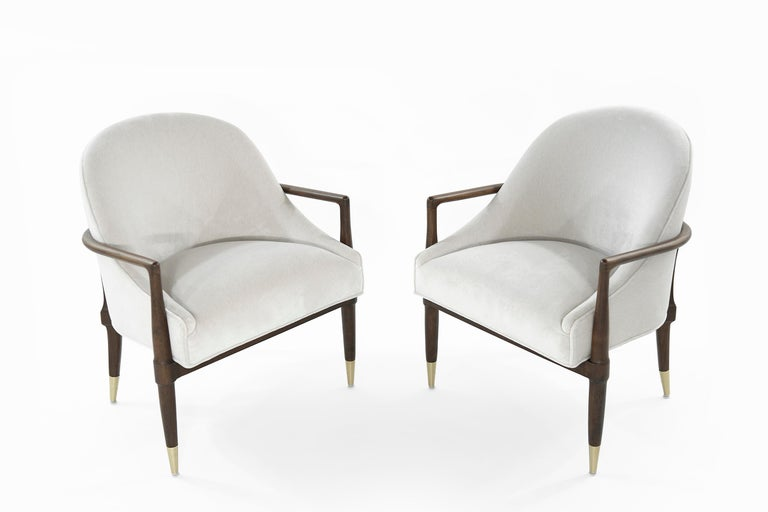 Pair of lounge chairs in the style of T.H. Robsjohn-Gibbings for Widdicomb. Featuring completely restored sculptural walnut frames and brass sabots. Newly upholstered in off-white velvet by Holly Hunt.