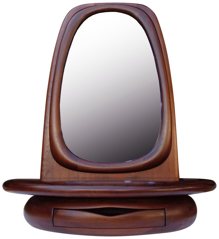 For your consideration is this beautifully sculpted mirror by Dean Santner.  This hand sculpted piece is the perfect entryway mirror or vanity. Featuring a sensualy carved oval frame with attached shelf that conceals a leather lined drawer. Perfect