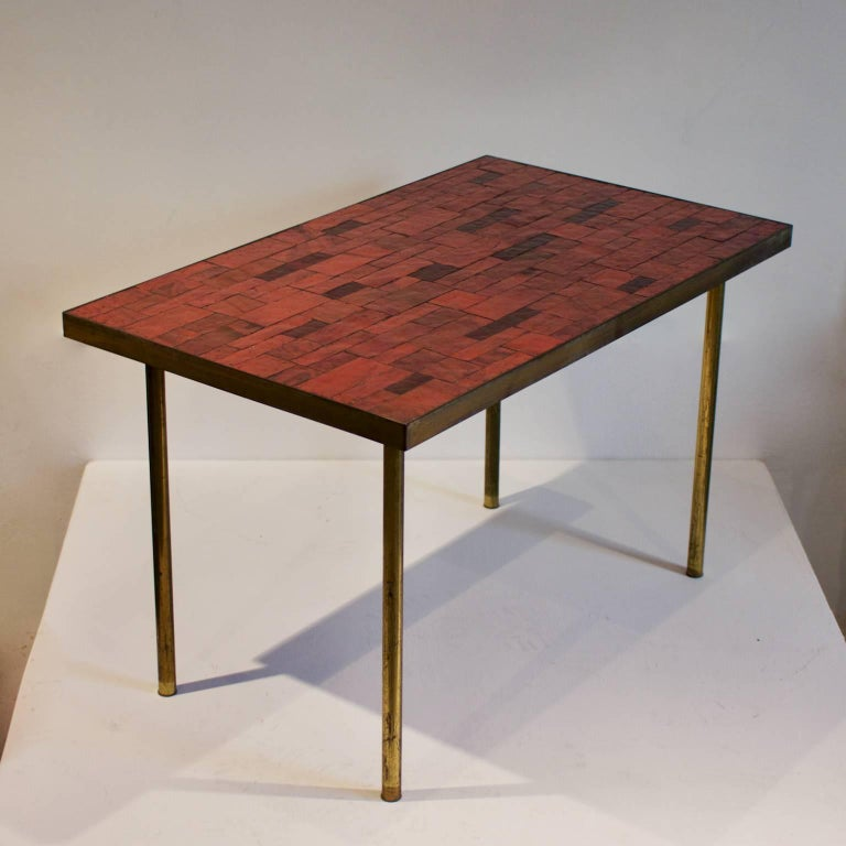 *** Please contact us for availability of this piece. ***  A mosaic side table in warm red tones, by Berthold Müller, Germany, mid-20th century.  The table is covered in rectangular stone mosaic tiles on wood, with a bronze or brass surround. The