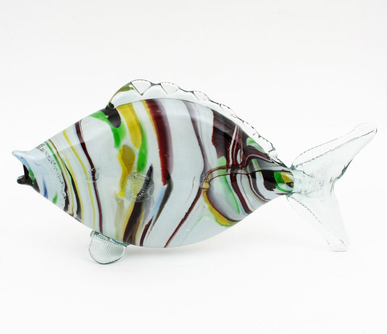 Fun hand blown Murano glass fish sculpture with a clear and white body and colorful strippes is yellow, green, garnet and brown. A beautiful Murano glass fish figure to place alone or with other Murano glass fishes creating a fun composition.