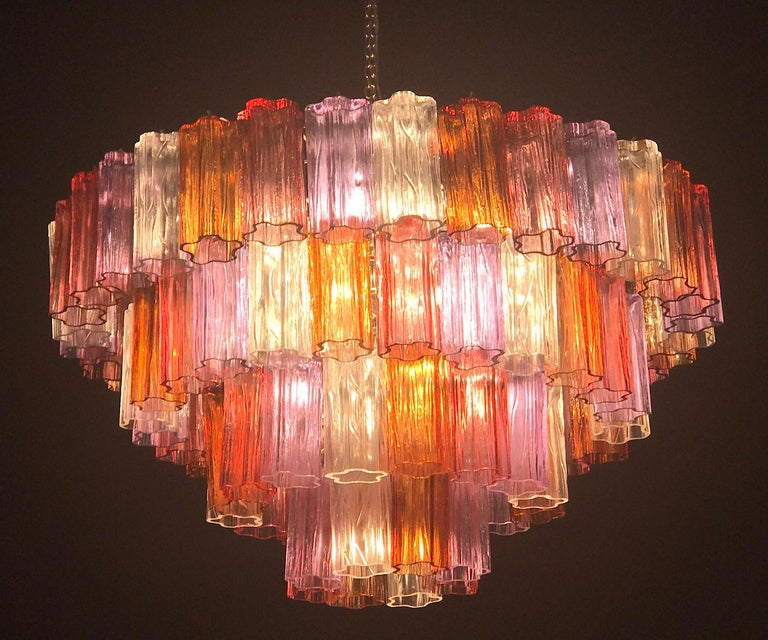 This amazing chandelier with rare color combination considering the uniqueness with amber, pink, amethyst, and ice color precious Murano glasses. Each chandelier with 80 glass blown elements supported by a chrome frame. 12 E 14 light bulbs.