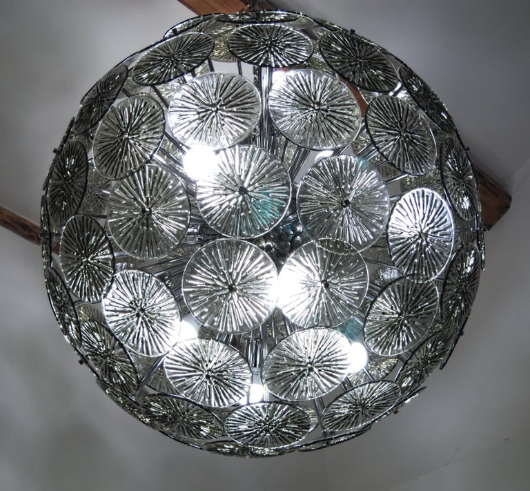Perfect sphere created by almost 100 elements of gray acciaio glass. Each element is hold by a chrome metal rod to recreate a perfect sphere. Two available to match in a large living room.  There are 12 standard sockets/bulbs to give the right