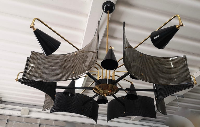 Extraordinary and original design for a midcentury Murano chandelier. Particular the manufacture of the glass combined with a shiny brass finish.  The structure of the chandelier is in brass, while the large plates are in black Murano glass.