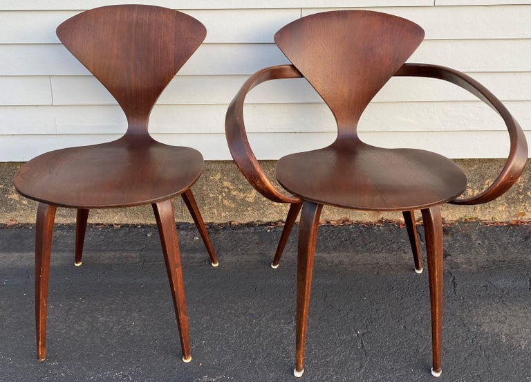 A nice midcentury set of five stylish pretzel walnut bentwood chairs, four side chairs and one arm chair, with round dining table with tapered legs, designed by Norman Cherner for Plycraft. The table is expandable, but no leaves are included. The