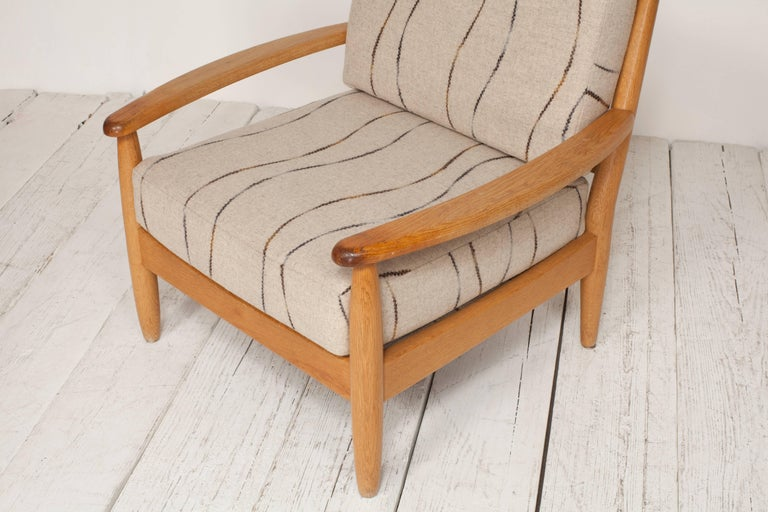 Midcentury oak spindle chair newly upholstered in grey wool fabric.