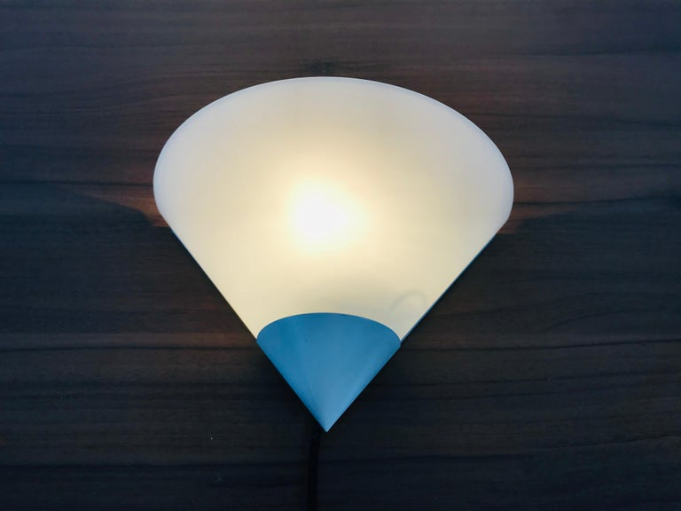 A beautiful Mid-Century Modern wall lamp by Glashütte Limburg made in Germany in the 1970s. It has a beautiful triangle shape and is made of aluminium and opaline glass. The back is white metal.