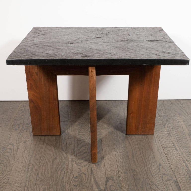 This refined and sophisticated table was realized  by the esteemed designer Adrian Pearsall for Craft Associates in the United States, circa 1960. It features a rectangular slate top resting on four hand rubbed walnut legs that form a right angle at