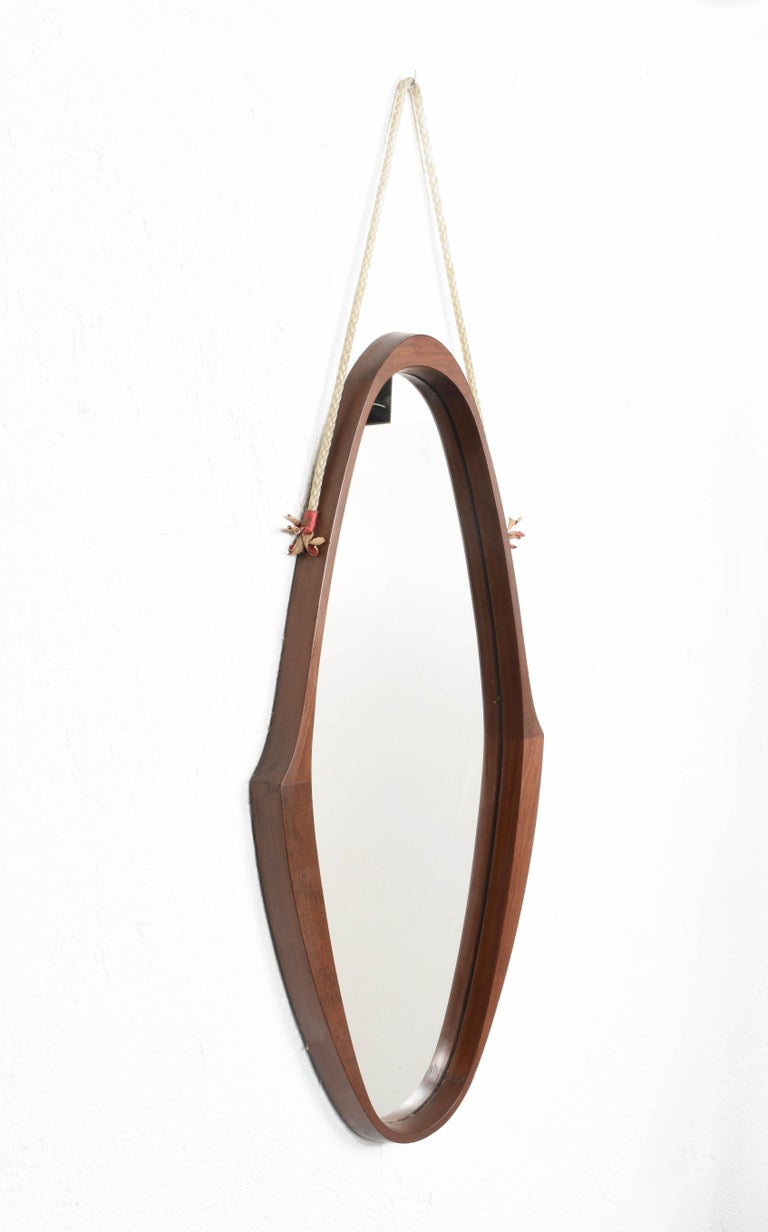 Amazing midcentury teak, nylon rope and leather oval wall framed mirror. This wonderful piece was produced in Italy during the 1960s.  This item has an astonishing teak oval structure with a unique design, the structure seems floating thanks to