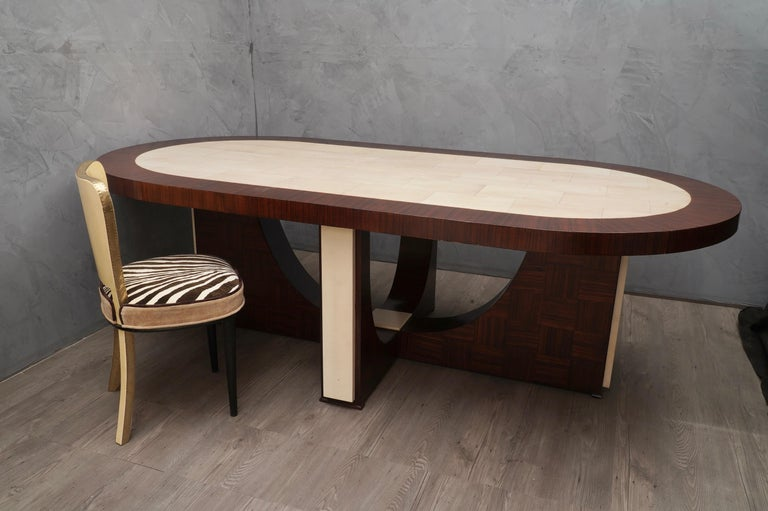 Clean lines and absolutely original shape for the leg with a very large tabletop, perfect for meetings in the office or in the family.  The tabletop is formed by a large zebrano wood veneered frame, with a goatskin covering in the center.