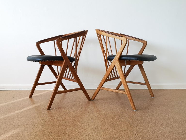 These chairs was designed by Bengt Ruda 1959 and produced by Ikea, Sweden. It made of oak with armrests made in teak. These one are considered a Classic piece for Ikea. The seat has been redone with leather imitation.  This is sold as a set of 2