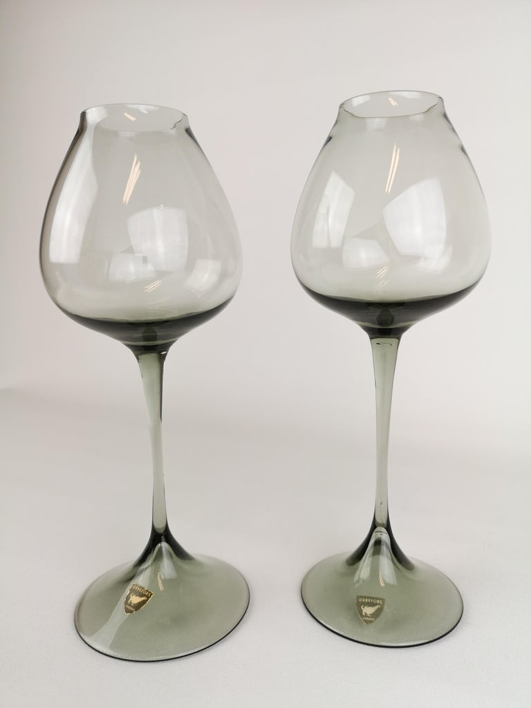 Wonderful pair of tulip glasses in grey tinted design. Manufactured at Orrefors in Sweden and design by Nils Landberg.  Good vintage condition and both are wearing a label.  Measures: H 22 D 8 cm.